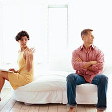 couple sitting on the bed, arguing