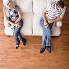 couple sitting on couch, turning away from each other